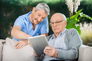 Caretaker with an elderly senior patient looking at an ipad