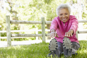 Elderly woman staying spry and healthy by stretching