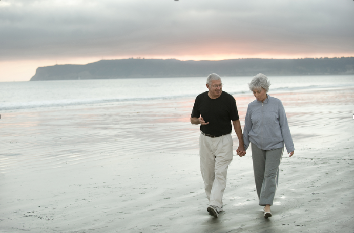 Elderly couple wearing comfortable walking shoes on the beach