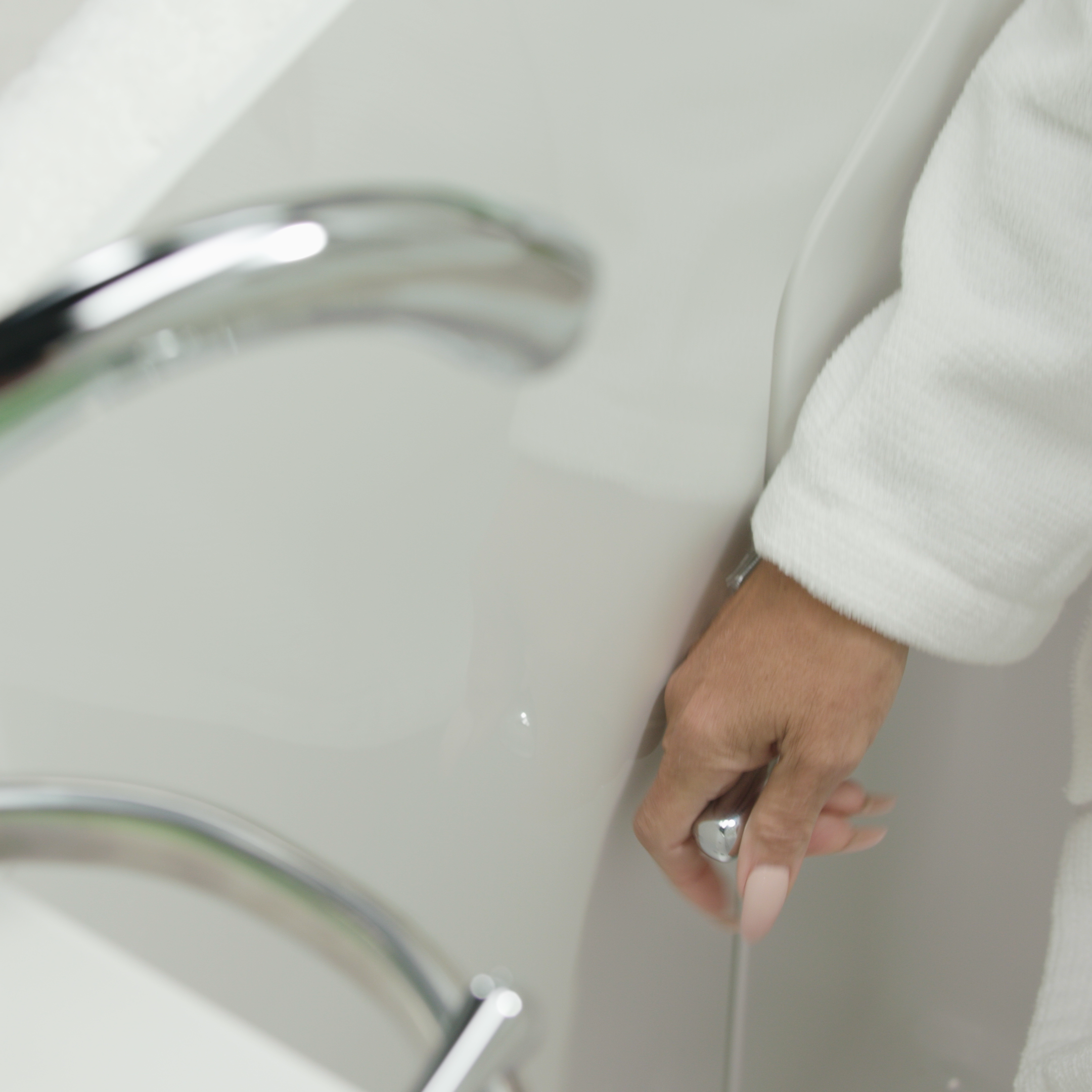 A tap being turned by an elderly woman in a walk-in tub